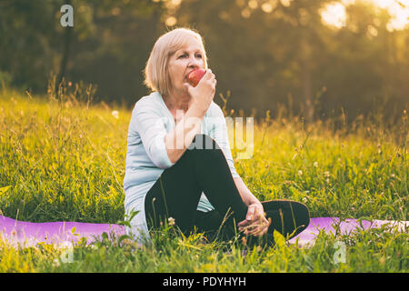 Active senior woman eating apple after exercise.Image is intentionally toned. - Stock Photo