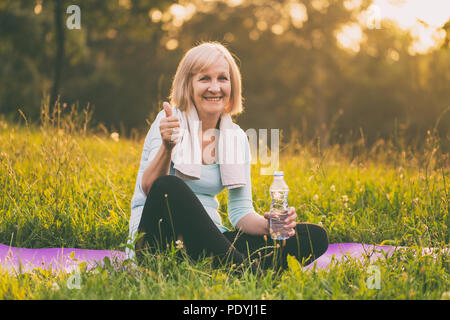 Active senior woman drinking water and showing thumb up during exercise.Image is intentionally toned. - Stock Photo
