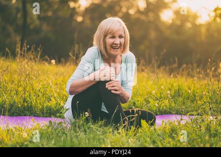 Senior woman having sport injury.Image is intentionally toned. - Stock Photo
