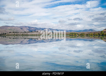 Sunset at Mount Cook National Park alongside Lake Pukaki with snow capped Southern Alps basking in the late winter afternoon's golden light. The setti - Stock Photo