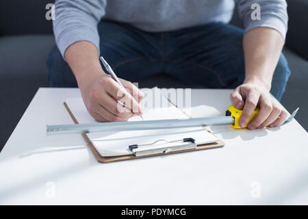 repair, building and home concept - close up of male hands writing in clipboard - Stock Photo