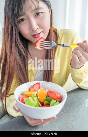 Portrait of attractive young woman sitting on sofa in a home family room living room, eating a fresh colorful salad, smiling. Girl eating healthy food - Stock Photo