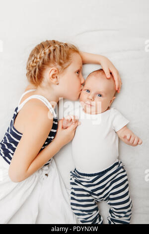 Lifestyle portrait of cute white Caucasian girl sister holding kissing little baby, lying on bed indoors. Older sibling with younger brother newborn.