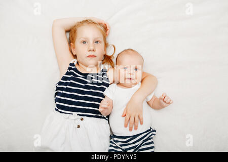 Lifestyle portrait of cute white Caucasian girls sister holding little baby, lying on bed. Older sibling with younger brother sister newborn looking i - Stock Photo