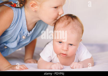 Lifestyle closeup portrait of cute white Caucasian girl sister kissing little baby, lying on bed indoors. Older sibling with younger brother newborn.  - Stock Photo
