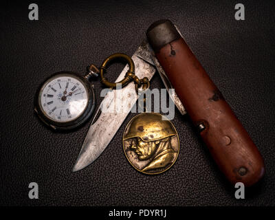 old soldier belongings vintage antique military pocket knife with pocket clock and soldier emplem white background world war 2 old - Stock Photo