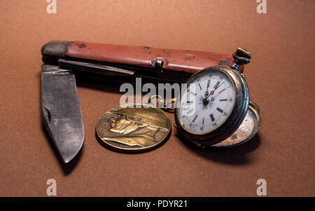 vintage antique military pocket knife with pocket clock and soldier emplem brown background world war 2 old - Stock Photo