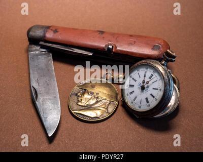old soldier belongings vintage antique military pocket knife with pocket clock and soldier emplem brown background world war 2 old - Stock Photo