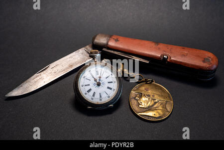 vintage antique swiss military pocket knife with pocket clock and soldier emplem white background world war 2 leather surface - Stock Photo