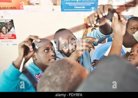 two young teenage Ugandan girls look at a roll of 35mm film during a photography lesson in a rural school - Stock Photo