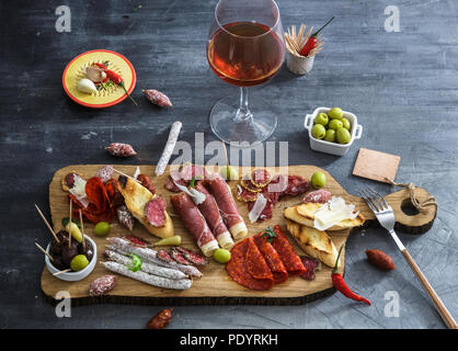 Typical spanish tapas concept. include variety slices jamon, chorizo, salami, bowls with olives, peppers. Copyspace. - Stock Photo