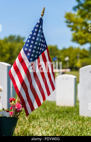 The United States National flag with white headstones in the background in Camp Butler National cemetery - Stock Photo