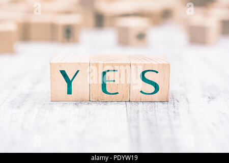 The Word Yes Formed By Wooden Blocks On A White Table - Stock Photo