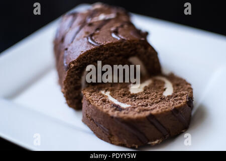 chocolate roll in icing on a white plate wooden table - Stock Photo