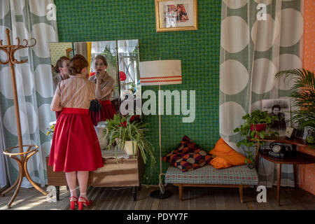 A Soviet girl makes a make-up at a mirror in her apartment. Reconstruction of the Khrushchev Thaw during the 'Times and Epoch' festival in Moscow - Stock Photo