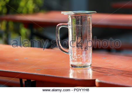 A pair of beer mats cover an empty beer glass in hot weather on a German evening - Stock Photo