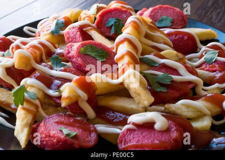 Homemade Peruvian Salchipapa Fries with Sausage Slices, Ketchup and Mayonnaise. Traditional Food. - Stock Photo
