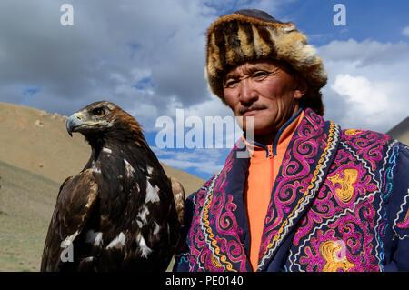 A Kazakh eagle hunter with his golden eagle in Bayan-Olgii, Mongolia. - Stock Photo