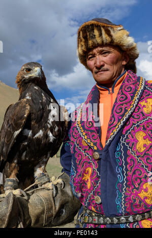 A Kazakh eagle hunter with his golden eagle in Bayan-Olgii, Mongolia. - Stock Photo