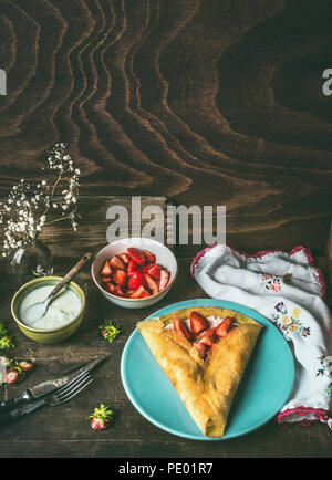 Homemade crepes on dark rustic kitchen table with strawberries and yogurt . Country style food still life - Stock Photo