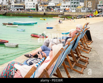 ST IVES, ENGLAND - JUNE 19: Older people, on vacation, sitting in a row of deckchairs in St Ives harbour, Cornwall. In St Ives, England. On 19th June  - Stock Photo
