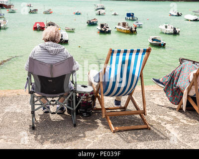 ST IVES, ENGLAND - JUNE 19: OAP couple sitting in deckchairs, enjoying the sun, in St Ives harbour. In St Ives, England. On 19th June 2018. - Stock Photo