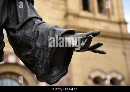 A bronze statue of Saint Francis of Assisi stands in front of the Cathedral Basilica of St. Francis of Assisi in Santa Fe, New Mexico. - Stock Photo