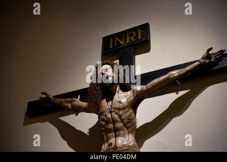 A wooden Crucifix mounted on a wall in the Cathedral Basilica of St. Francis of Assisi in Santa Fe, New Mexico - Stock Photo