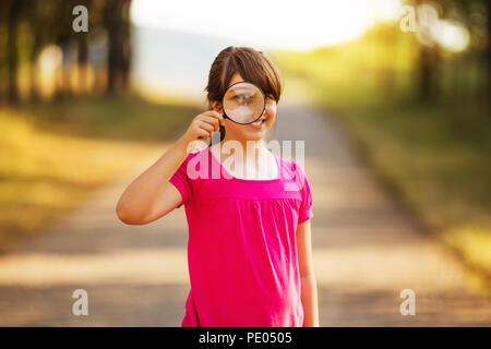 Beautiful little girl looking through magnifying glass in the nature.Image is intentionally toned. - Stock Photo