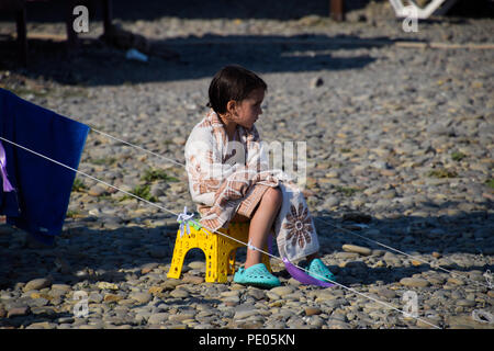 Novorossiysk, Russia - August 06, 2018: The girl sits on a chair near a tent wrapped in a blanket. - Stock Photo