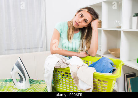 Woman is displeased because she has got to much laundry for ironing. - Stock Photo