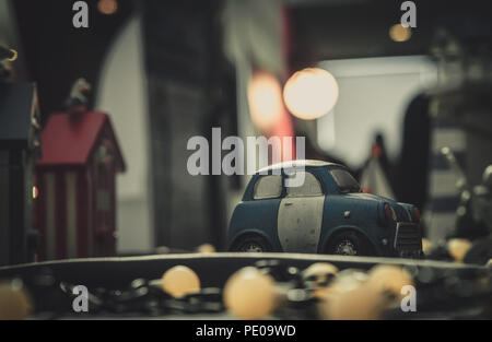 Blue and white small car toy model on the road. Mini car toy in the city near building on blurred background  with bokeh. Cartoon miniature car. World - Stock Photo