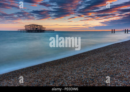 The old destroyed West Pier in Brighton, UK, after sunset - Stock Photo