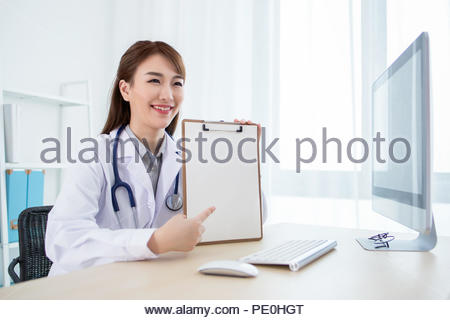 Attractive aisan doctor working in office - Stock Photo