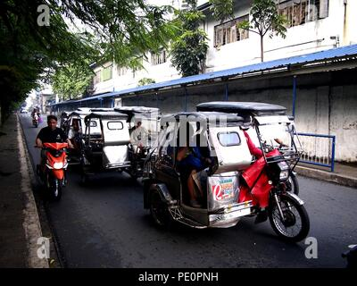 ANTIPOLO CITY, PHILIPPINES: AUGUST 4, 2018: Tricycles and motorcycles pass along a busy road in Antipolo City. - Stock Photo