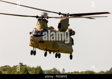 A U.S. Army CH-47 Chinook helicopter takes off during Leapfest 2018 at the University of Rhode Island in West Kingston, R.I., Aug. 5, 2018. Leapfest is the largest, longest-standing, international static line parachute training event and competition hosted by the 56th Troop Command, Rhode Island Army National Guard, to promote high level technical training and esprit de corps within the International Airborne community. Over 300 Paratroopers from nine different countries will participate this year. (U.S. Army photo by Staff Sgt. Justin P. Morelli) - Stock Photo