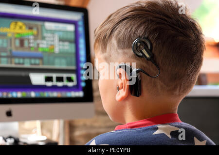 Rear back view of boy child with cochlear implants looking at screen playing a computer game in the UK    KATHY DEWITT - Stock Photo