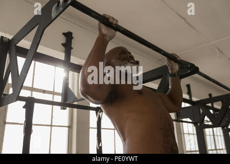Senior man exercising pull up on a pull up bar in the fitness studio - Stock Photo