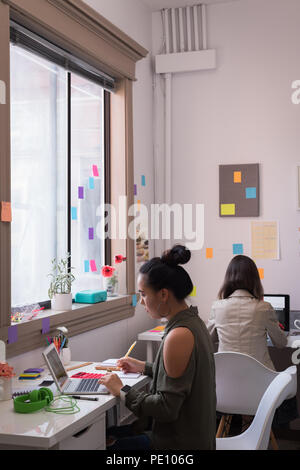 Fashion designers working on laptop in design studio - Stock Photo