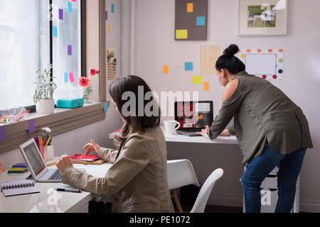 Fashion designers working on laptop in design studio - Stock Photo