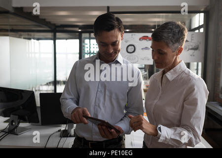 Business colleagues discussing over digital tablet - Stock Photo