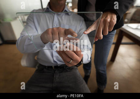 Business colleagues using glass digital tablet - Stock Photo