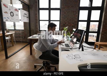 Businessman using glass digital tablet at desk - Stock Photo