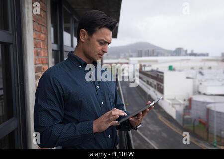 Businessman using digital tablet in balcony