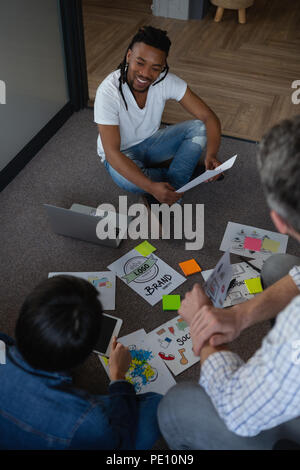 Colleagues discussing over documents - Stock Photo