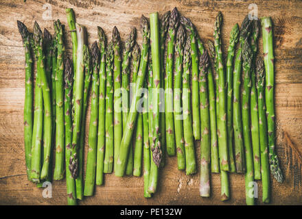 Raw uncooked green asparagus in row over wooden background - Stock Photo