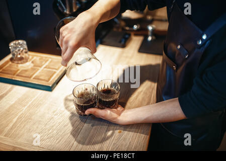 Young male barista makes fresh black coffee at cafe counter. Barman works in cafeteria, bartender prepares espresso - Stock Photo
