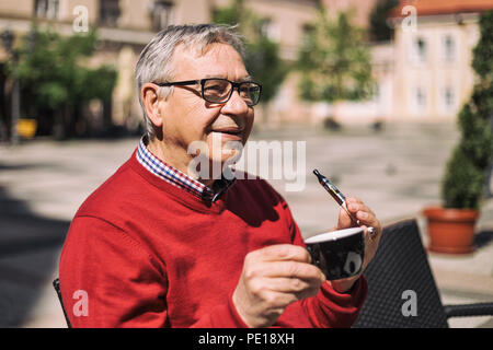 Cheerful senior man enjoys drinking coffee and smoking electronic cigarette at the bar.Image is intentionally toned. - Stock Photo