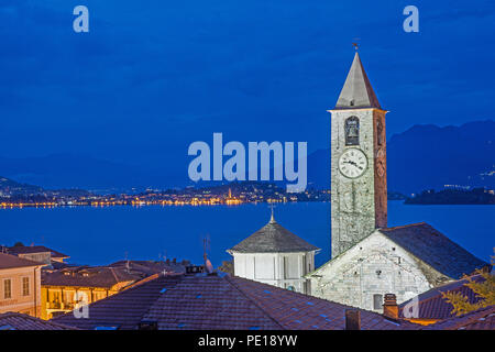 Blue hour view from roof top terrace of Hotel Rosa Baveno Italy with view of church clock tower and Lago Maggiore showing floodlit church and sparklin - Stock Photo