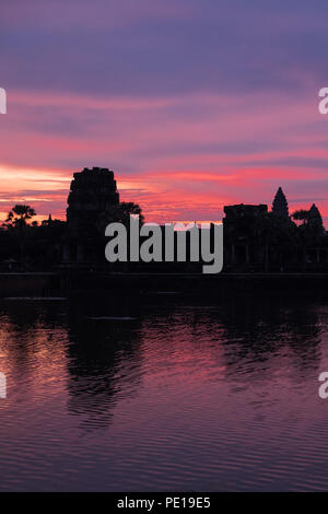 Sunrise over the moat surrounding the temple Angkor Wat - the largest religious monument in the world - near Siem Reap, Cambodia - Stock Photo